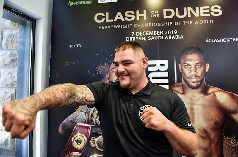 """Mexican-American heavyweight boxing champion Andy Ruiz Jr throws a punch into the air as he poses before a poster of the upcoming """"Clash on the Dunes"""" fight between him and British challenger Anthony Joshua, set to take place in December, at a press conference in Diriya on the western outskirts of the Saudi capital Riyadh on September 4, 2019. - The """"Clash on the Dunes"""" is scheduled to take place in Diriya on December 7. (Photo by Fayez Nureldine / AFP) (Photo credit should read FAYEZ NURELDINE/AFP/Getty Images)"""