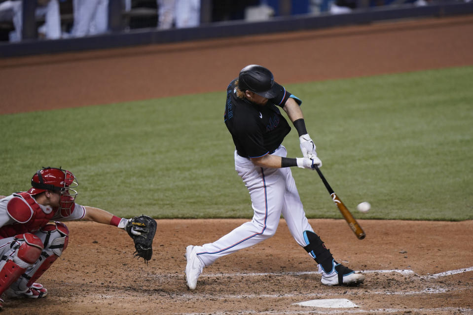 Miami Marlins' Chad Wallach hits a home run, also scoring Miguel Rojas, during the sixth inning of the second game of a baseball doubleheader against the Philadelphia Phillies, Sunday, Sept. 13, 2020, in Miami. (AP Photo/Wilfredo Lee)