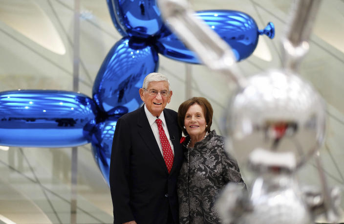 """FILE - In this Sept. 16, 2015 file photo, Eli Broad and his wife, Edythe, stand for a photo amid Jeff Koons sculptures at his new museum called """"The Broad"""" in downtown Los Angeles. Eli Broad, the billionaire philanthropist, contemporary art collector and entrepreneur who co-founded homebuilding pioneer Kaufman and Broad Inc. and launched financial services giant SunAmerica Inc., died Friday, April 30, 2021 in Los Angeles. He was 87. (AP Photo/Richard Vogel, File)"""
