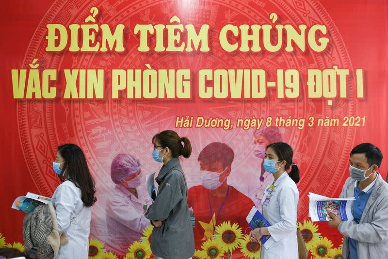 FILE PHOTO: Health workers wait for their turn as Vietnam starts its official rollout of AstraZeneca's COVID-19 vaccine, in Hai Duong