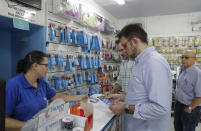 Customers buy masks at a medical supply store, to wear as a precaution against the spread of the new coronavirus COVID-19, in Sao Paulo, Brazil, Wednesday, Feb. 26, 2020. Brazil's government confirmed on Wednesday that a Brazilian man who traveled to Italy this month has Latin America's first confirmed case of the contagious new coronavirus. (AP Photo/Andre Penner)