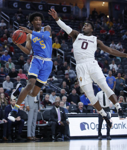 UCLA's Chris Smith, left, passes around Arizona State's Luguentz Dort during the first half of an NCAA college basketball game in the quarterfinals of the Pac-12 men's tournament Thursday, March 14, 2019, in Las Vegas. (AP Photo/John Locher)