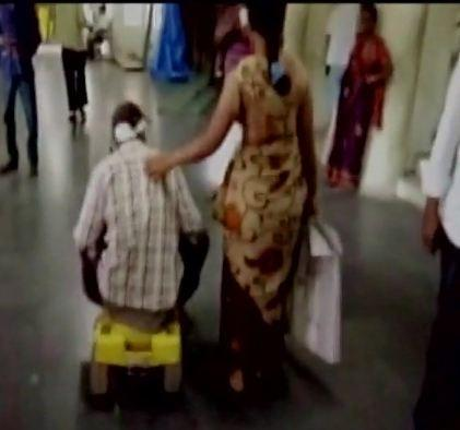 Raju pushing around on his son's tricycle while his wife Santoshi helps him