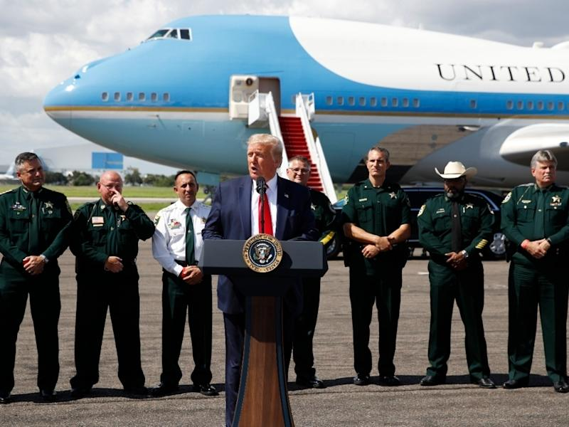 With Air Force One in the background, President Donald Trump speaks Tampa International Airport during a campaign event with the Florida Sheriffs Association in Tampa Friday.