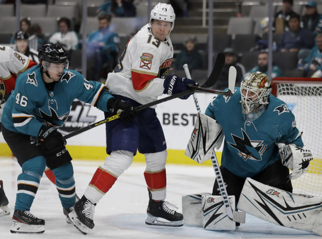 San Jose Sharks' Joel Kellman, left, and goalie Aaron Dell, right, defend against Florida Panthers' Mark Pysyk (13) in the second period of an NHL hockey game Monday, Feb. 17, 2020, in San Jose, Calif. (AP Photo/Ben Margot)