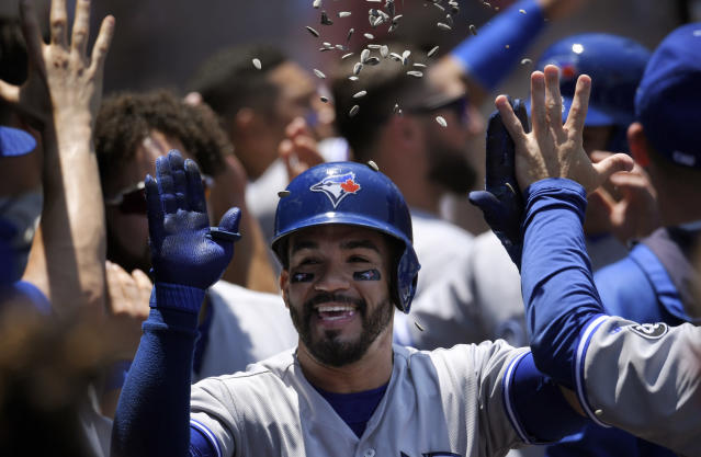 Toronto Blue Jays' Devon Travis, center, is congratulated by teammates after hitting a three-run home run during the second inning of a baseball game against the Los Angeles Angels Sunday, June 24, 2018, in Anaheim, Calif. (AP Photo/Mark J. Terrill)