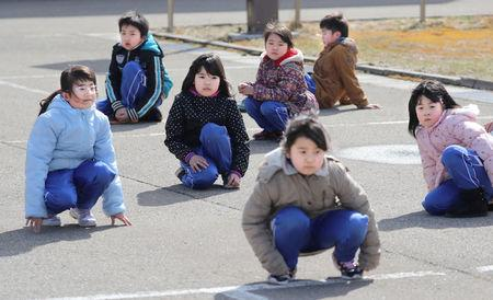 Elementary school students squat down on the street as they participate in an evacuation drill for local residents based on the scenario that a ballistic missile launched landed in Japanese waters, in Oga