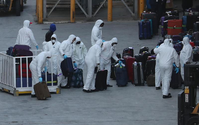 Workers dressed in hazmat suits take the luggage of Zaandam - Getty