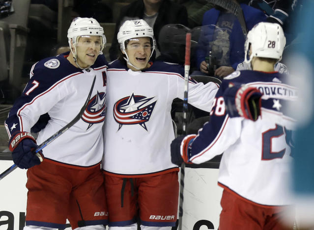 Columbus Blue Jackets' Sonny Milano, center, is hugged by teammate Jack Johnson, left, after Milano scored against the San Jose Sharks during the first period of an NHL hockey game, Sunday, March 4, 2018, in San Jose, Calif. (AP Photo/Marcio Jose Sanchez)