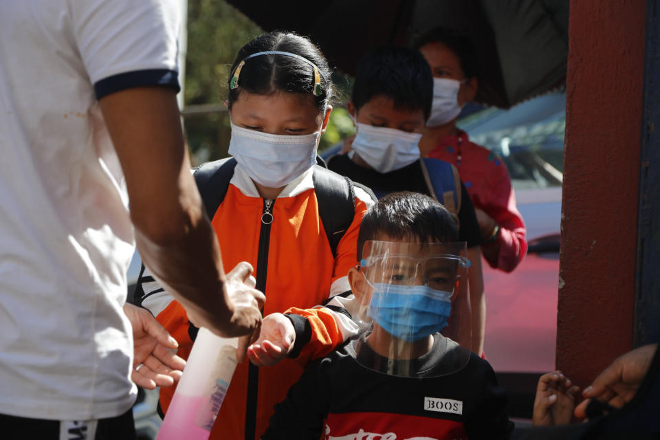 A door man gives hand sanitizer as Nepalese children arrive at their school that reopened after being closed for months due to the COVID-19 pandemic in Kathmandu, Nepal, Monday, Sept. 27, 2021. (AP Photo/Niranjan Shrestha)