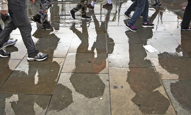 Members of the public walk through heavy rain in Westminster, London (Picture: PA)