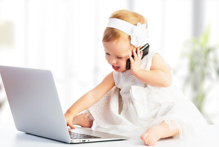 A baby holding a smartphone while playing with laptop