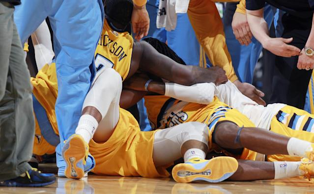 Denver Nuggets guard Randy Foye, center, is mobbed by teammates J.J. Hickson, left, and Kenneth Fried, right, after Foye fell on the court following his 3-point basket with nine-tenths of a second remaining in the fourth quarter to seal the Nuggets' 116-115 victory over the Los Angels Clippers in an NBA basketball game in Denver, Monday, Feb. 3, 2014. (AP Photo/David Zalubowski)