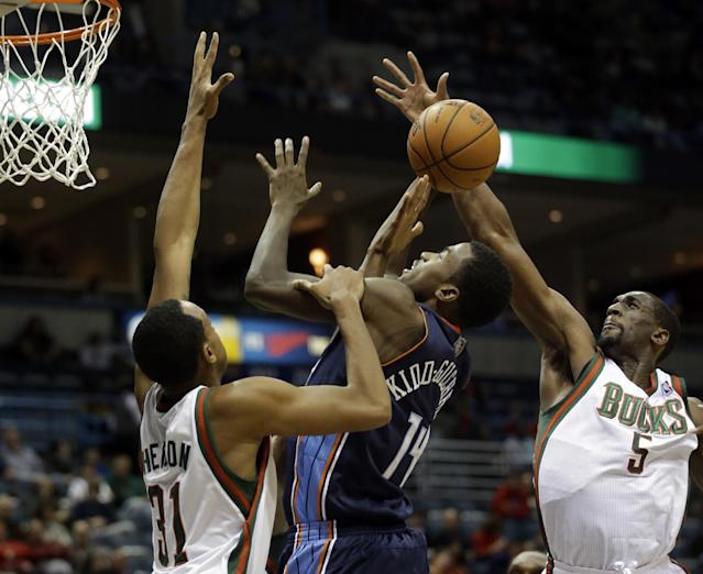 Charlotte Bobcats' Michael Kidd-Gilchrist (14) shoots between Milwaukee Bucks' John Henson (31) and Ekpe Udoh (5) during the first half of an NBA basketball game on Saturday, Nov. 23, 2013, in Milwaukee. (AP Photo/Morry Gash)