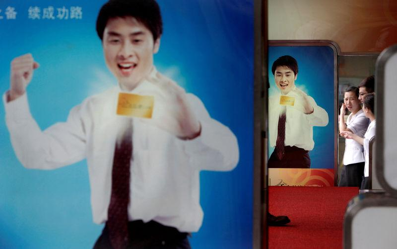 FILE PHOTO: Office workers walk past an advertisement for a credit card in the centre of Shanghai