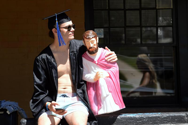 """BOULDER, CO - MAY 7: A University of Colorado Boulder student, not identified, holds a praying statue while having a graduation party outside of a home in the University Hill area of Boulder. Boulder County's """"Stay-at-home order"""" expires on May 8. (Photo by Jeremy Papasso/MediaNews Group/Boulder Daily Camera via Getty Images)"""