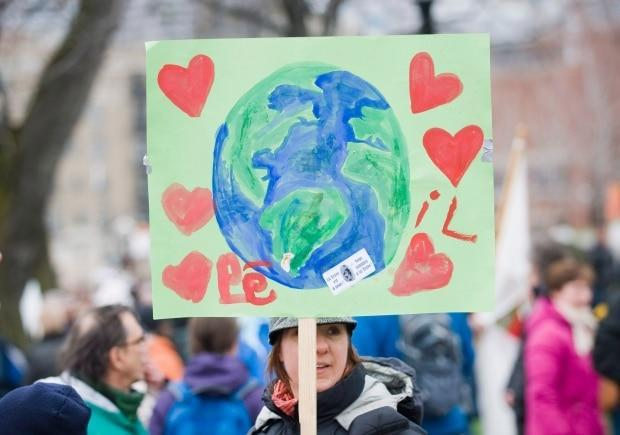 A woman holds a sign at a 2012 rally in Montreal to mark international Earth Day. A social worker suggests talking frankly with children about their climate change concerns.  (Graham Hughes/The Canadian Press - image credit)