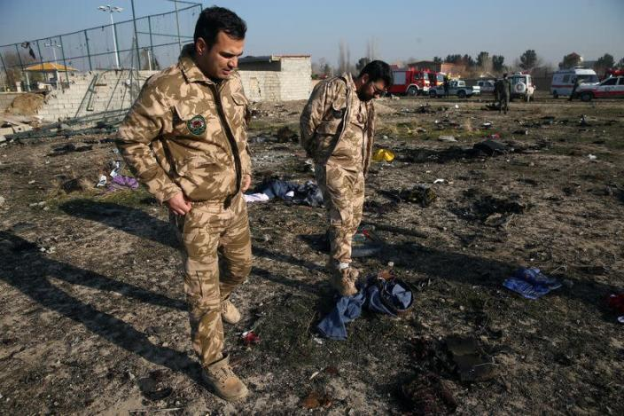 Security look at passengers' belongings at the site where the Ukraine International Airlines plane crashed after take-off from Iran's Imam Khomeini airport, on the outskirts of Tehran