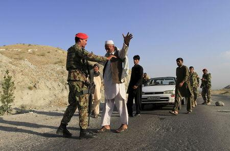Afghan National Army soldiers (ANA) inspect passengers at a checkpoint on the outskirts of Jalalabad province, eastern Afghanistan, June 29, 2015. REUTERS/Parwiz