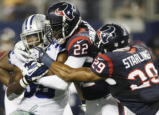 Dallas Cowboys running back Joseph Randle (35) is tackled by Houston Texans defensive back Roc Carmichael (22) and Jawanza Starling (29) during the first half of a preseason NFL football game Thursday, Aug. 29, 2013, in Arlington, Texas. (AP Photo/Tony Gutierrez)