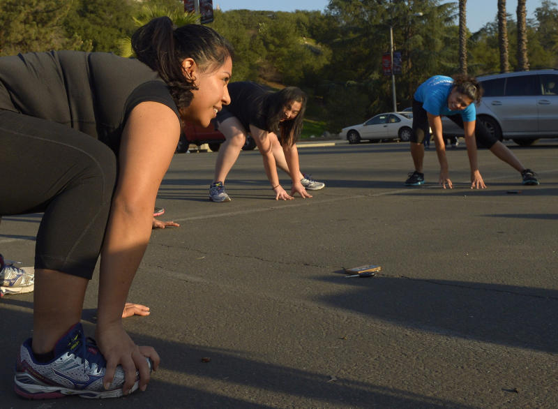 In this Tuesday, Dec. 11, 2012 photo, Zendi Solano, left, stretches with her running club in Pasadena, Calif. Dr. Robert Sallis says doctors with Kaiser Permanente, one of the nation's largest nonprofit health insurance plans, generally prescribe exercise first, instead of medication, and for many patients who follow through, that's often all it takes. (AP Photo/Mark J. Terrill)
