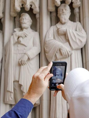 A passerby takes a photograph of the defaced statue of Confederate commander General Robert E. Lee, at Duke University's Duke Chapel in Durham, North Carolina, U.S. August 17, 2017. REUTERS/Jonathan Drake