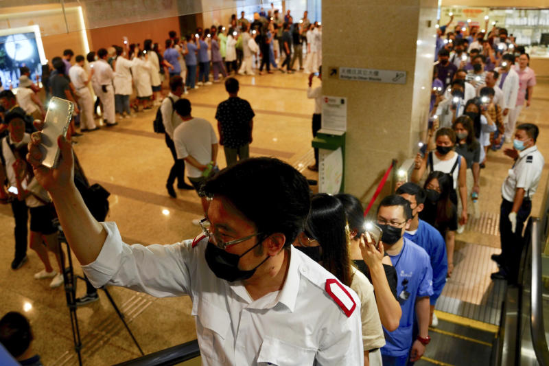 Medical workers show their palm with five fingers, signifying the five demands of protesters and chanted slogans as they stood in the foyer of the hospital before moving to different floors of the building at the Prince of Wales Hospital in Hong Kong, Monday, Sept. 16, 2019. The anti-government protests have taken place since June and increasingly have been marked by violence and clashes with police. (AP Photo/Vincent Yu)