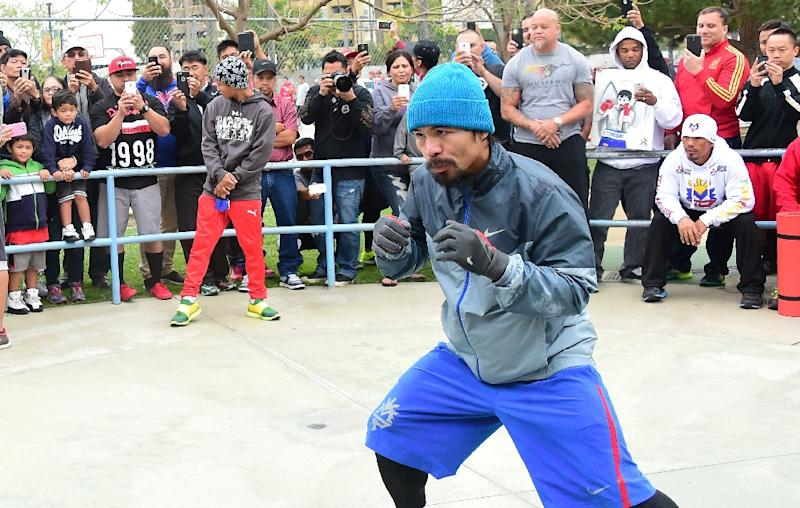 A crowd gathers to watch as boxer Manny Pacquiao shadow boxes during a work out at a park following his morning jog in Los Angeles, California on April 21, 2015 (AFP Photo/Frederic J. Brown)