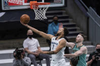 Memphis Grizzlies forward Kyle Anderson (1) lays up the ball past Charlotte Hornets forward Gordon Hayward during the first half of an NBA basketball game in Charlotte, N.C., Friday, Jan. 1, 2021. (AP Photo/Jacob Kupferman)