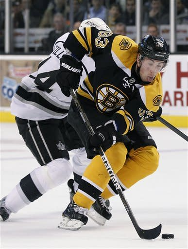 Boston Bruins left wing Brad Marchand (63) beats Los Angeles Kings right wing Justin Williams (14) to the puck in the second period of an NHL hockey game in Boston Tuesday, Dec. 13, 2011. (AP Photo/Elise Amendola)