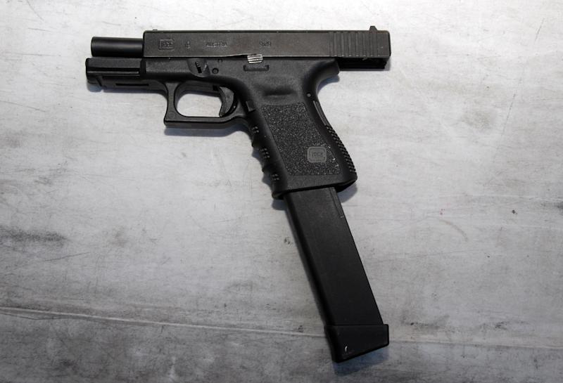In this image released by the Pima County Sheriff's department, a Glock 9mm gun with an extended magazine is seen in the aftermath of the Tucson shooting rampage that killed six people and wounded former U.S. Rep. Gabrielle Giffords and 12 others in January 2011.  Authorities released more than 300 photos on Tuesday, May 21, 2013, made by investigators during their investigation in the parking lot of the shopping center where the shooting took place.  (AP Photo/Pima County Sheriff)