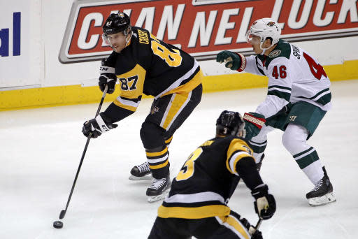 Pittsburgh Penguins' Sidney Crosby (87) looks to pass the puck as Minnesota Wild's Jared Spurgeon (46) defends during the first period of an NHL hockey game in Pittsburgh, Tuesday, Jan. 14, 2020. The Penguins won 7-2. (AP Photo/Gene J. Puskar)