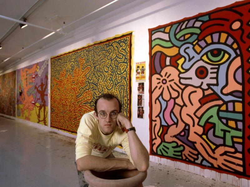 Radical pop artist Keith Haring crouches in front of his paintings, circa 1985: Rex Features