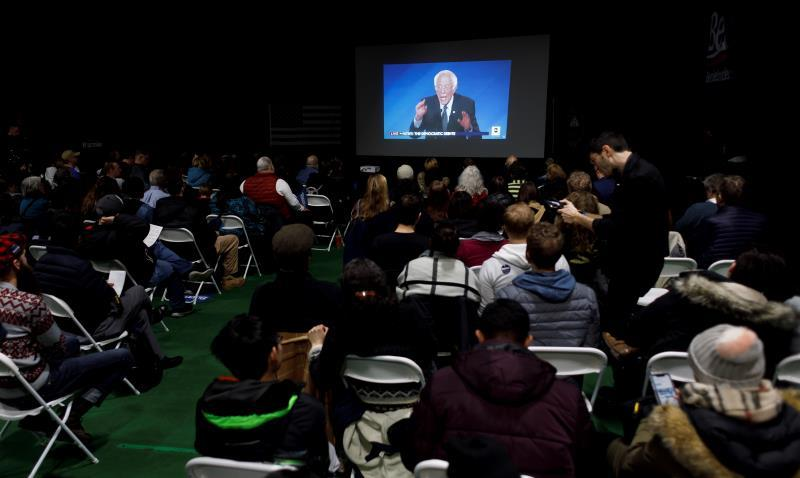 People watch as US presidential candidate Senator Bernie Sanders participates in a Democratic presidential debate on a screen during a debate watch party organized by the Sanders' campaign, in Manchester, New Hampshire, USA, 07 February 2020. EFE/EPA/JUSTIN LANE