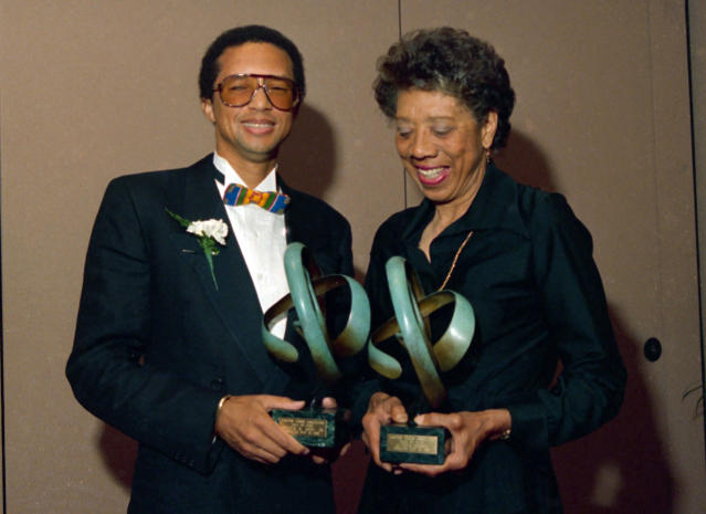 FILE - In this May 13, 1988, file photo, tennis players Arthur Ashe, left, and Althea Gibson pose while holding trophies after being inducted into the Eastern Tennis Association Hall of Fame in New York. Gibson won an amazing 11 Grand Slam titles in three years from 1956-58, including the French Open, Wimbledon and U.S. Open. On Monday, Aug. 26, 2019, the USTA will unveil a statue in her honor at the U.S. Open. (AP Photo/Susan Ragan, File)