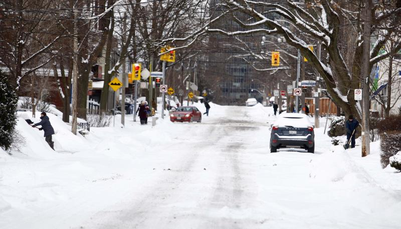 Residents dig out of the snow following an overnight snow storm in Toronto, Ontario