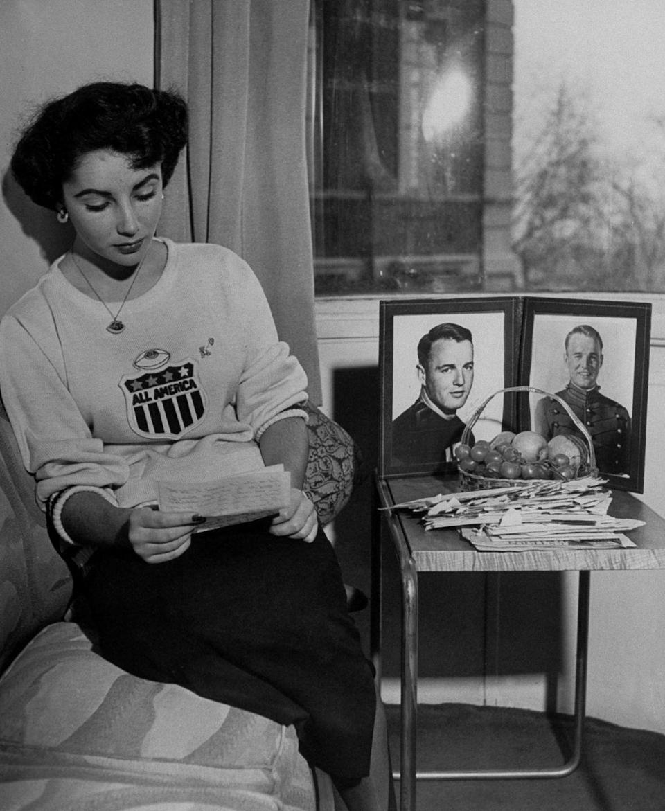 <p>Elizabeth is seen reading a letter from her overseas boyfriend, Glenn Davis, next to a portrait of him. The young couple broke up later that year. </p>