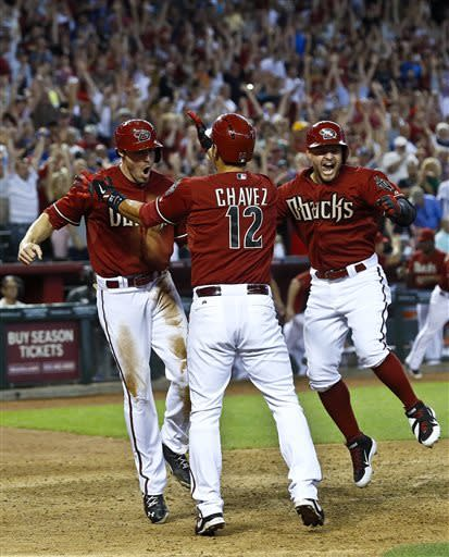 Arizona Diamondbacks' A.J. Pollock, left, celebrates his game-winning run against the Los Angeles Dodgers with teammates Eric Chavez (12) and Cody Ross during the ninth inning in a baseball game on Sunday, April 14, 2013 in Phoenix. The Diamondbacks defeated the Dodgers 1-0. (AP Photo/Ross D. Franklin)