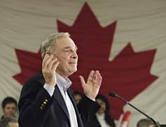 Paul Martin gestures while making a speech with the Canadian flag in the background.