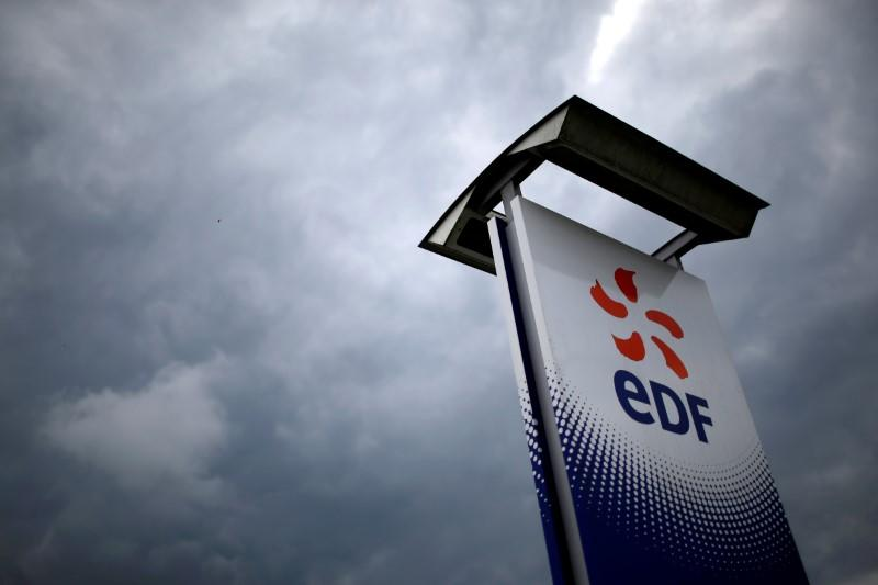 FILE PHOTO: The logo of France's state-owned electricity company EDF is seen next to the Electricite de France (EDF) thermal electricity production plant in Cordemais