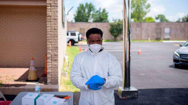 PHOTO: A health care worker puts on additional personal protective equipment at a COVID-19 testing site at United Memorial Medical Center in Houston, on July 9, 2020. (Mark Felix/AFP via Getty Images)
