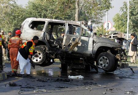 Rescue personnel inspect a vehicle damaged by a suicide bomber which killed a senior Pakistani police official on his way to work in Peshawar, Pakistan November 24, 2017. REUTERS/Fayaz  Aziz
