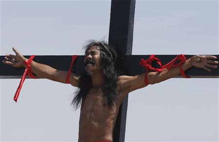 A penitent nailed to a cross grimaces during a re-enactment of the death of Jesus Christ on Good Friday in San Fernando, Pampanga in northern Philippines April 18, 2014. REUTERS/Erik De Castro