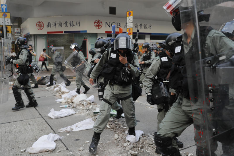 Riot police cross barricade made by protesters during a protest in Hong Kong, Saturday, Oct. 12, 2019. Protesters marching peacefully hit the rain-slickened streets of Hong Kong again in multiple locations on Saturday, defying police warnings that they were gathering illegally. (AP Photo/Kin Cheung)