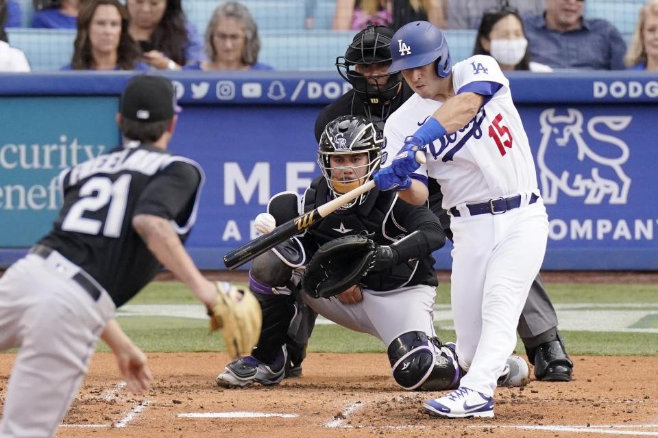 Los Angeles Dodgers' Austin Barnes, right, hits a solo home run as Colorado Rockies starting pitcher Kyle Freeland, left, watches along with catcher Dom Nunez, second from left, and home plate umpire Vic Carapazza during the second inning of a baseball game Saturday, July 24, 2021, in Los Angeles. (AP Photo/Mark J. Terrill)