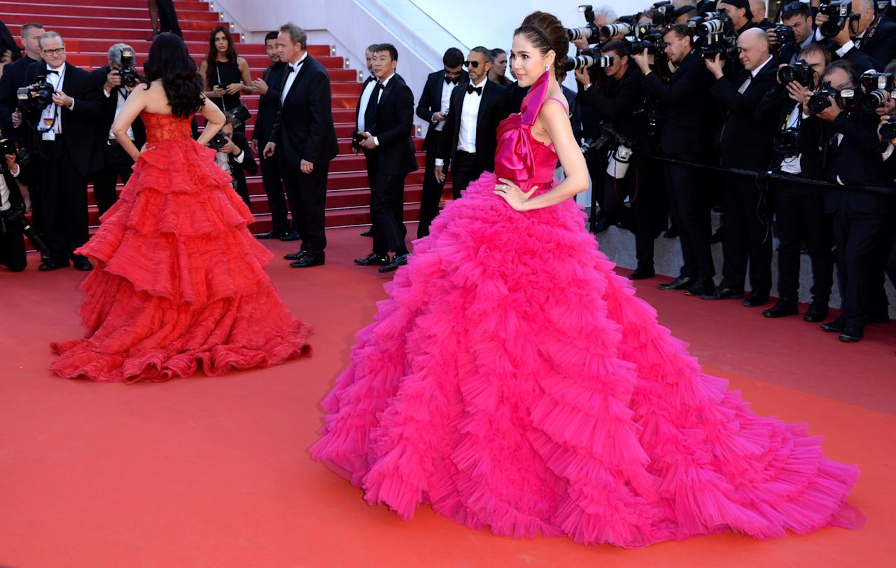 <p>Thai actress Arya Hargate went for big, bright, and bold with this bowed gown from Zuhair Murad for the <em>120 Beats Per Minute</em> screening. Aishwarya Rai poses in the background in a Ralph & Russo design. (Photo: Getty Images) </p>