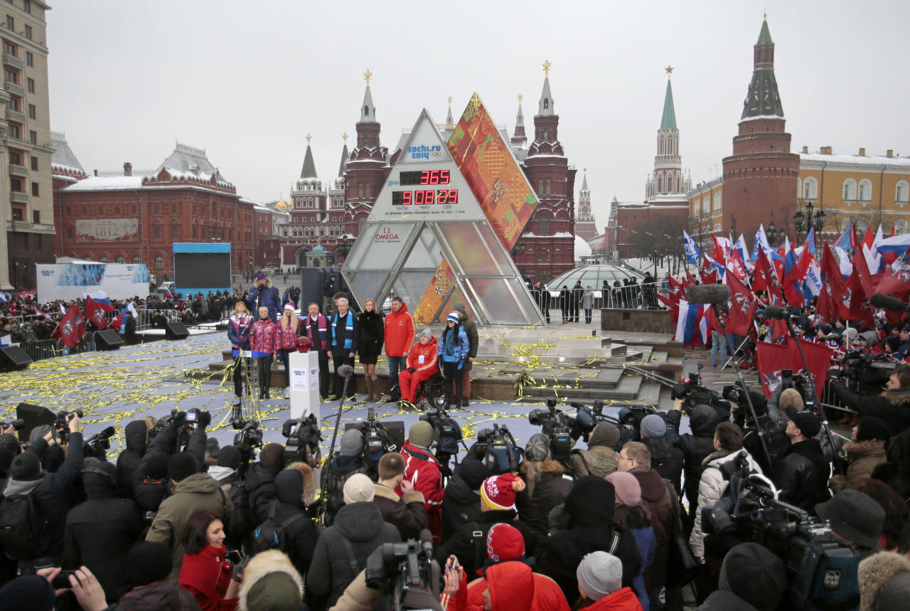 Moscow's Mayor Sergei Sobyanin, center, stands surrounded by a crowd of various sports enthusiasts waving Russian and Moscow flags during a ceremony of the launching the one-year count down clock for the upcoming 2014 Sochi Olympics, in Moscow, Russia, Thursday, Feb. 7, 2013. (AP Photo/Mikhail Metzel)