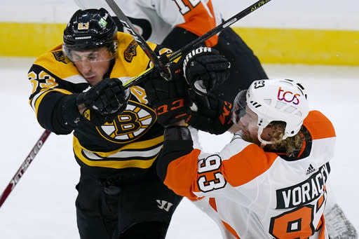 Boston Bruins center Brad Marchand (63) grapples with Philadelphia Flyers right wing Jakub Voracek (93) during the third period of an NHL hockey game Thursday, Jan. 21, 2021, in Boston. (AP Photo/Elise Amendola)
