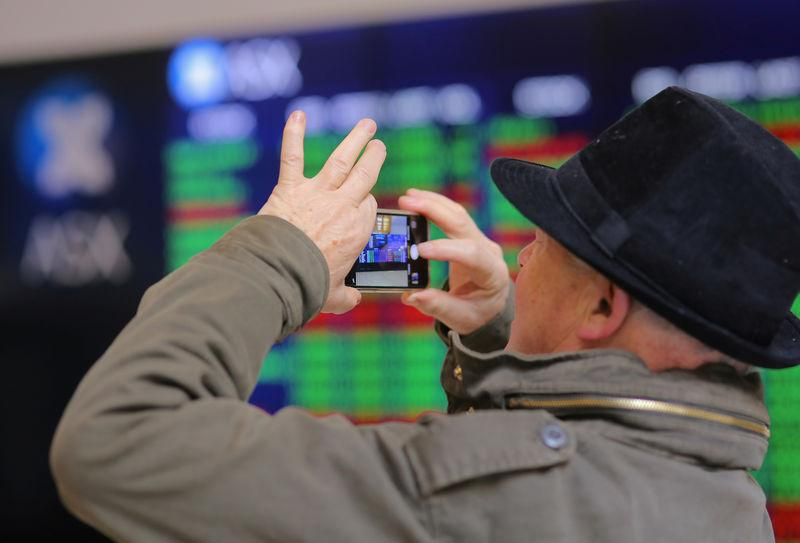 An investor takes a photograph using his phone as he stands in front a board displaying stock prices at the Australian Securities Exchange in Sydney