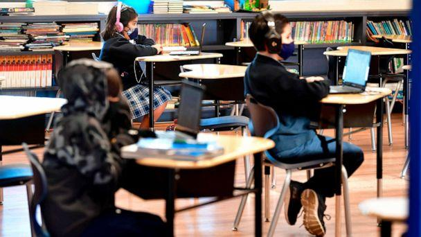 PHOTO: Students sit with their laptop computers at St. Joseph Catholic School in La Puente, Calif., Nov. 16, 2020, where pre-kindergarten to Second Grade students in need of special services returned to the classroom today for in-person instruction. (Frederic J. Brown/AFP via Getty Images, FILES)